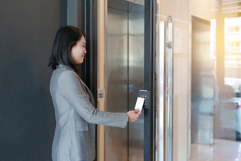 Woman using access control to building
